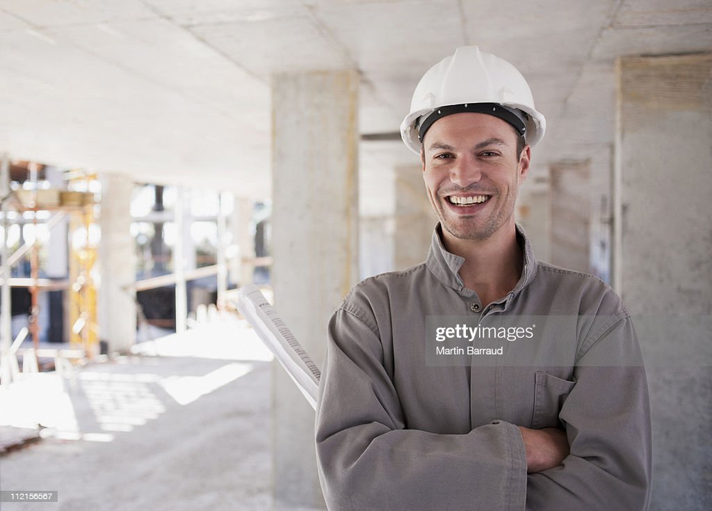 Construction worker with arms crossed on construction site : Stock Photo