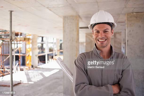Trabajador de la construcción con los brazos cruzados en solar de construcción