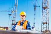 Builder in reflective vest and hardhat standing at construction site and holding digital tablet