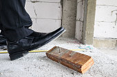Construction worker with leather shoes steps on nail at house building site, work accident concept