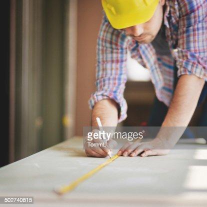 Travailleur de la Construction avec ruban à mesurer sur place