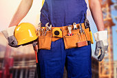 close up of construction worker with tool belt at building site