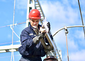 Electrician with hadhat, protective workwear and protective gloves working in power plant.