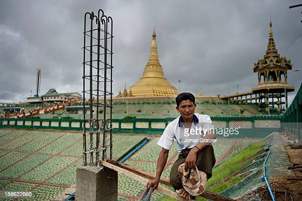 A construction worker working on a construction site in Naypyidaw In the background is Uppatasanti Pagoda a 325 feet high golden replica of the world...