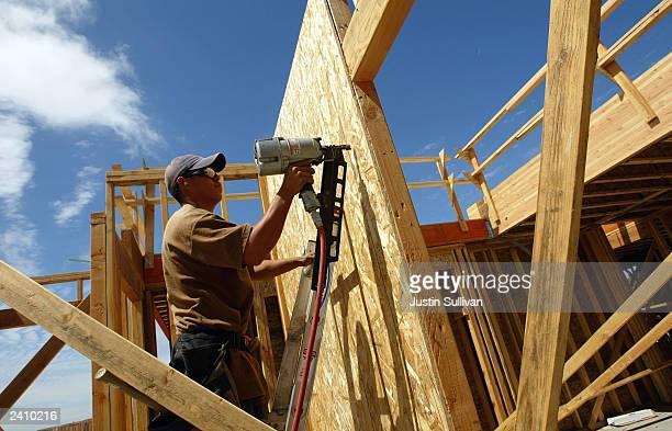 A construction worker works on the framing of a new home August 19 2003 in Rodeo California New home construction jumped in July to its highest level...