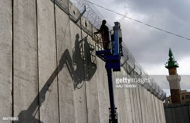 Construction workers add a barb wired fence on top of the eight meter concrete wall part of Israel's security barrier in the divided West Bank...