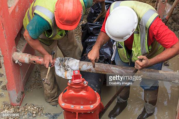 Construction workers adjusting gate valve position on water main