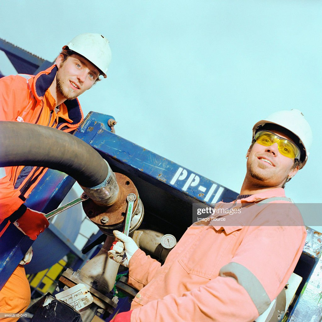 Construction workers adjusting pipe : Stock Photo