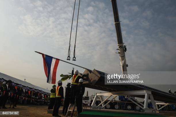 Construction workers anchor one of the steel cornerstones of the funeral pyre for the late Thai King Bhumibol Adulyadej to a crane next to the Grand...
