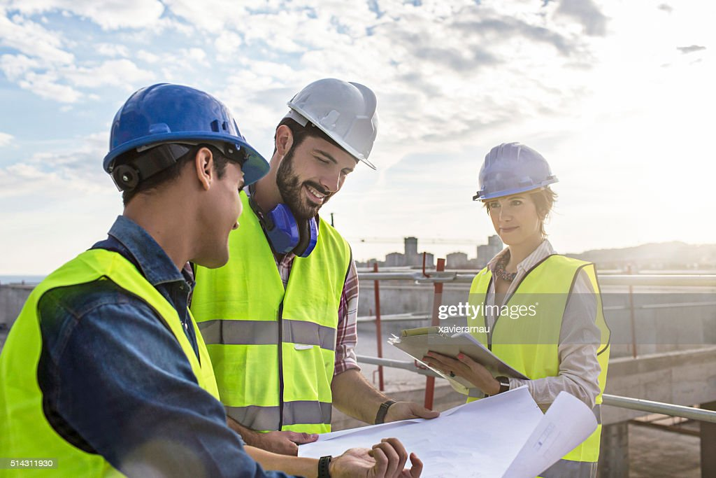 Construction workers and architect looking at blueprints on construction site : Stock Photo