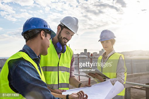 Construction workers and architect looking at blueprints on construction site