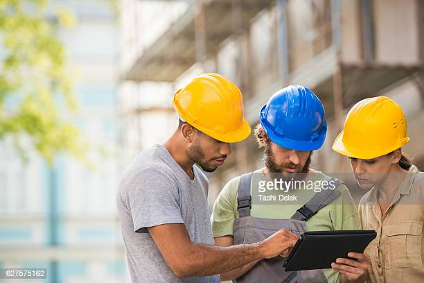 Construction Workers And Architect Reviewing Plans