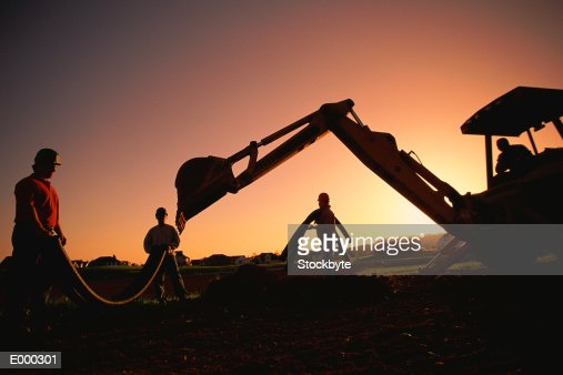 Construction workers and backhoe at sunset : Stock Photo