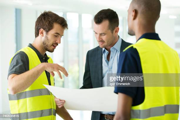 Construction workers and businessman, looking at plans