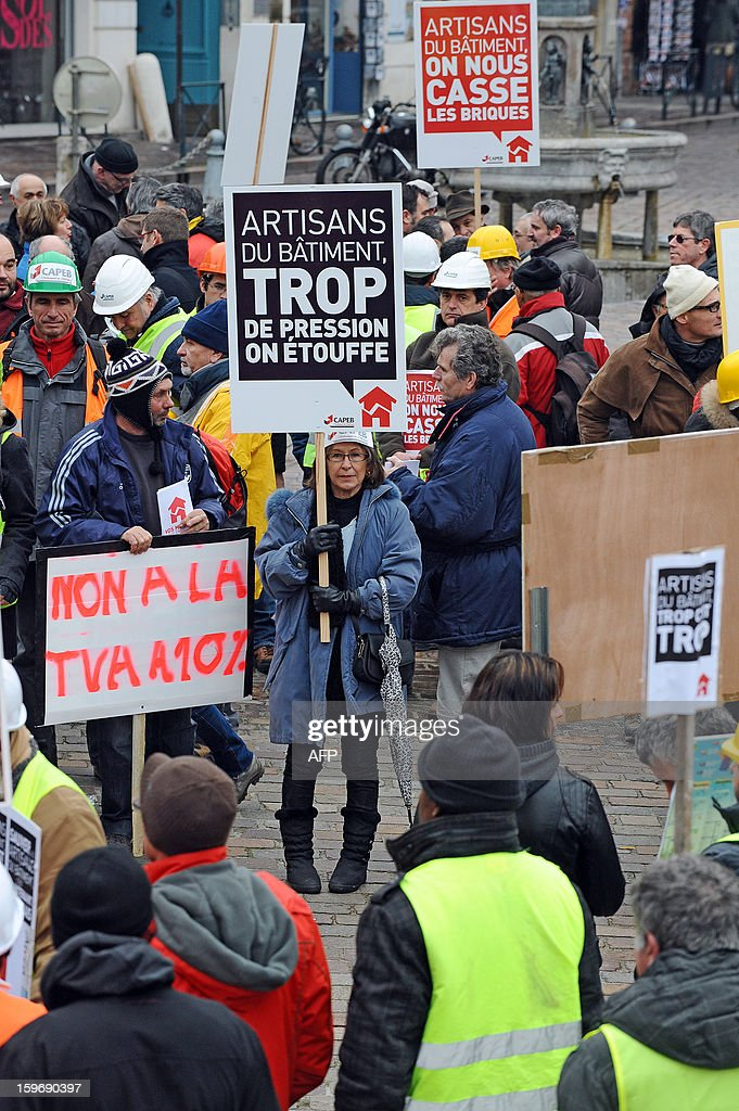 Construction workers and professionals in the building sector hold signs reading ''No to the VAT at 10%' and '' professionals in the building sector, too much pressure, we suffocate'' during a demonstration called by the CAPEB, a French union for small-sized craft enterprises, to denounce the increase of the rate of the value added tax (VAT) from seven to ten percent, on January 18, 2013 in Toulouse. Under plans designed to boost the country's competitiveness, the Socialist administration announced 20 billion euros of tax breaks for businesses that will be partly financed by increases in VAT from January 1, 2014. AFP PHOTO/REMY GABALDA