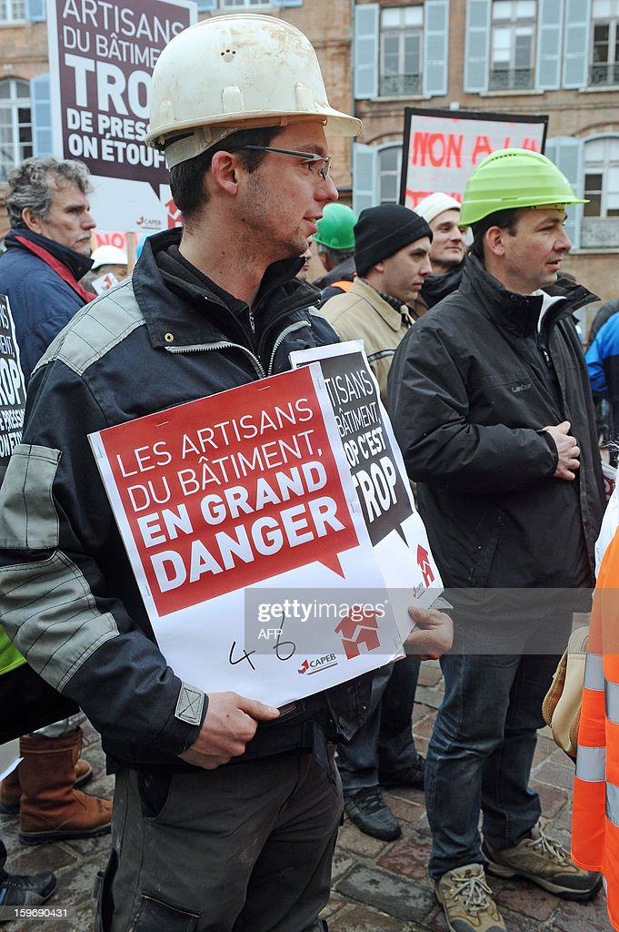 Construction workers and professionals in the building sector hold signs reading ''professionals in the building sector, in great danger'' during a demonstration called by the CAPEB, a French union for small-sized craft enterprises, to denounce the increase of the rate of the value added tax (VAT) from seven to ten percent, on January 18, 2013 in Toulouse. Under plans designed to boost the country's competitiveness, the Socialist administration announced 20 billion euros of tax breaks for businesses that will be partly financed by increases in VAT from January 1, 2014. AFP PHOTO/REMY GABALDA