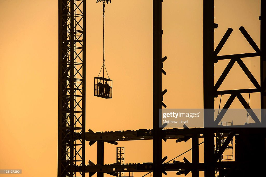 Construction workers are carried in a lift to their crane as work continues on the 122 Leadenhall St skyscraper, nicknamed the Cheesegrater, at sunrise on March 5, 2013 in London, England. The recent construction of numerous tall buildings on the London skyline has been controversial due to concerns that views of historic landmark buildings, such as St Paul's cathedral, are being obscured.