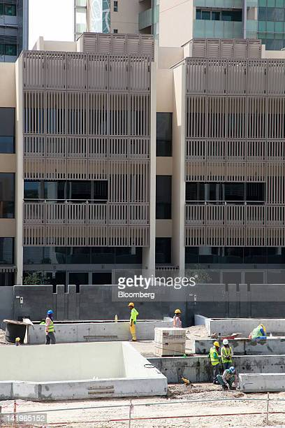Construction workers are seen building new apartment blocks at the Al Muneera development during a media tour organized by Aldar Properties PJSC Abu...