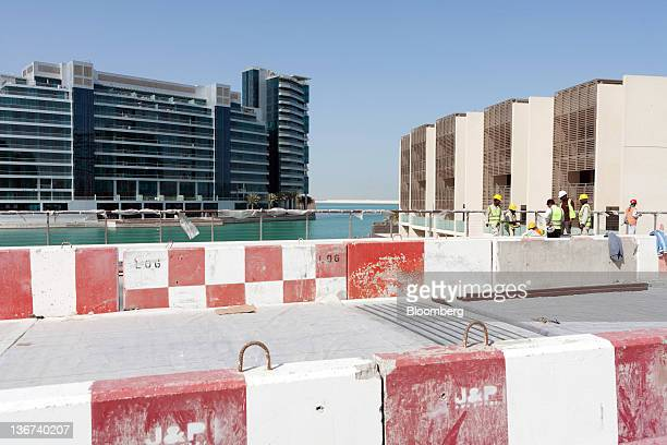 Construction workers are seen during the last phase of building at the Khor Al Raha beach development in Abu Dhabi United Arab Emirates on Tuesday...