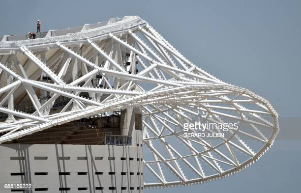 Construction workers are seen on the top of the Wanda Metropolitano Stadium in Madrid on May 24 the new stadium of Club Atletico de Madrid that is to...