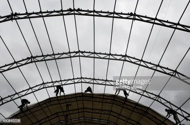 Construction workers are silhouetted as they set up a giant tent in Pristina on June 18 2014 that will serve to provide free 'Iftar' meals for poor...