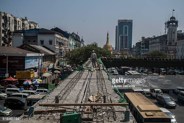 Construction workers at the entrance to the Sule Square in downtown Yangon on March 17 2016 in Yangon Burma Myanmar's foreign investment nearly...