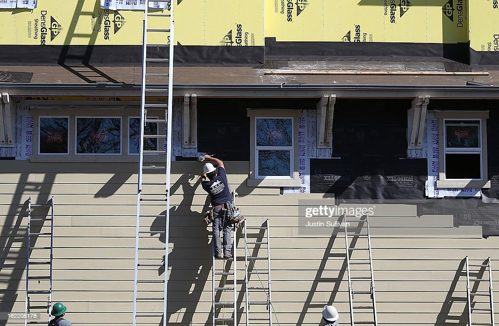 Construction workers attach siding to a new home at the Arbor Rose housing development on February 20, 2013 in San Mateo, California. The Commerce Department reported that new housing starts dropped 8.5% in January following a 15.7% increase one month earlier.