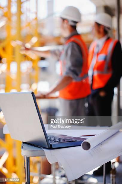 Bau Arbeiter hinter laptop und Werkzeuge in constructio