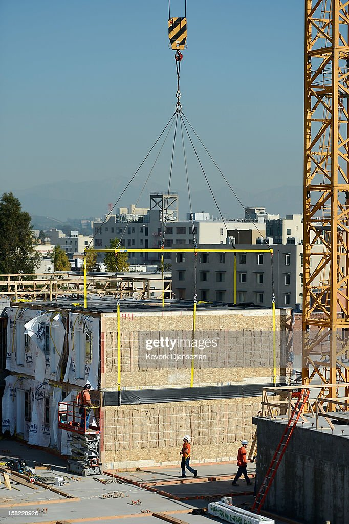 Construction workers build 102 prefabricated housing units placed atop the second floor of the Star Apartments building under construction by the Skid Row Housing Trust on December 11, 2012 in Los Angeles, California. The modular homes will become the first multi unit prefabricated homes in Los Angeles for formerly homeless and impoverished people.