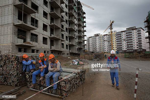 Construction workers build a new upscale apartment complex on June 10 2015 in Ulaanbaatar Mongolia A few years ago Mongolia boasted one of the...