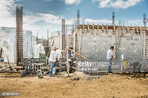 Construction workers building cinder block wall