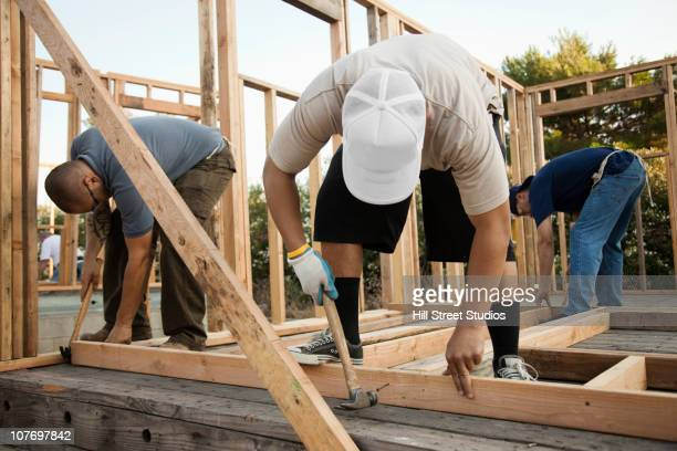 Construction workers building house frame