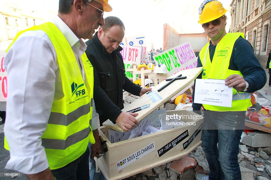 Construction workers carry a coffin with petitions after emptying rubble in front of the police station in Perpignan as they protest against high employer taxes on January 31, 2013. AFP PHOTO / RAYMOND