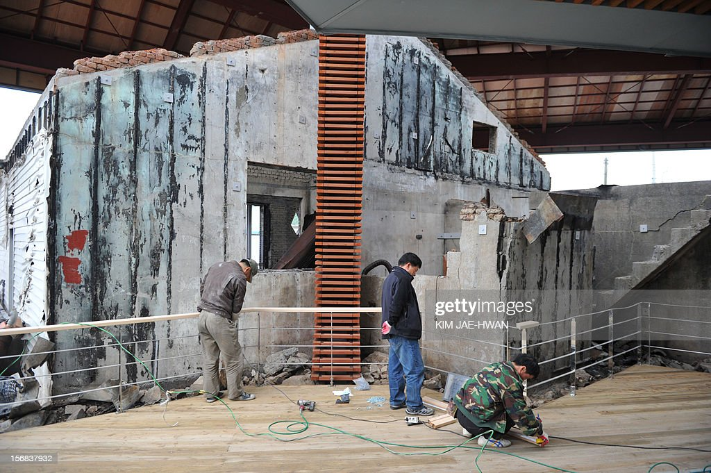 Construction workers carry out their duties at a new museum aimed at commemorating North Korea's 2010 shelling attack on Yeonpyeong island on November 23, 2010. The museum, which houses wreckage of two homes worst-hit by the 2010 shelling as well as images and videos detailing the attack, opens on November 23 marking the second anniversary of an attack that triggered fears of a full-scale conflict.