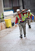 Construction workers carry scaffolding