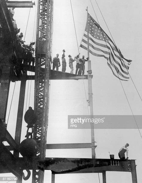Construction workers celebrate the completion of the iron work on the Empire State Building Manhattan circa 1930 The building was constructed between...