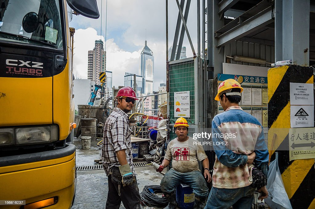 Construction workers chat at the entrance of a building site in front of the city's skyline in Hong Kong on November 22, 2012. Hong Kong's economy returned to modest growth in the third quarter, meaning the southern Chinese city avoided a technical recession, typically defined by GDP contractions in two consecutive quarters. AFP PHOTO / Philippe Lopez