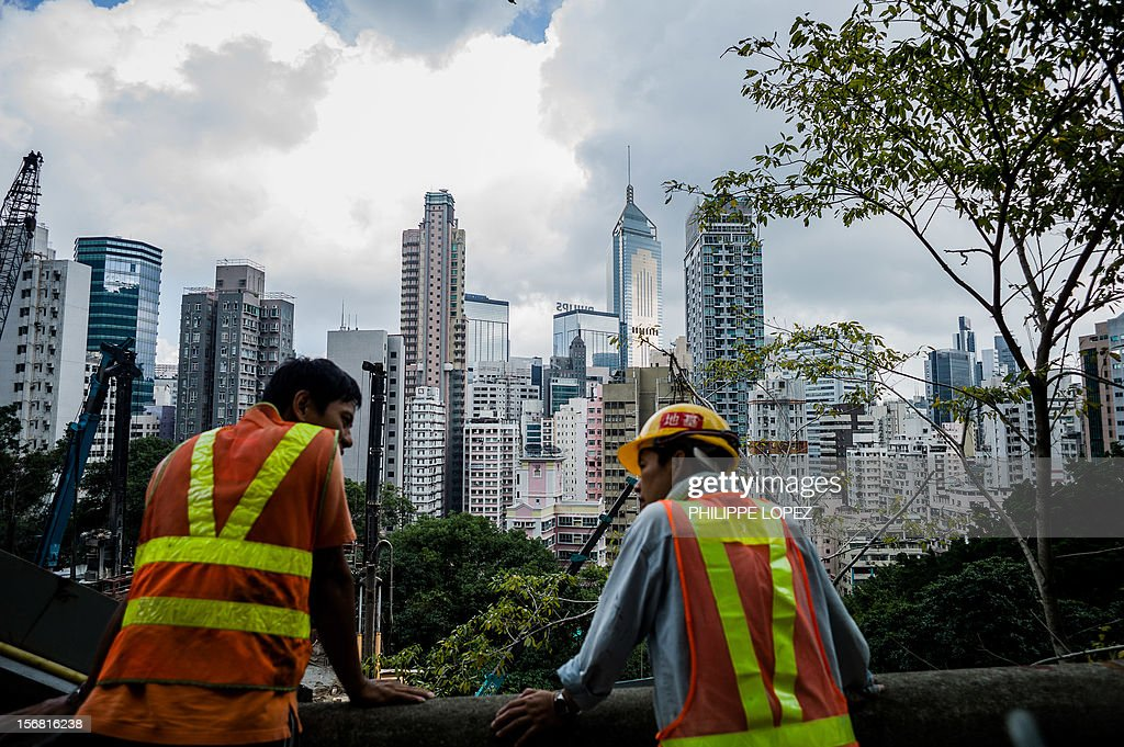 Construction workers chat in front of the city's skyline in Hong Kong on November 22, 2012. Hong Kong's economy returned to modest growth in the third quarter, meaning the southern Chinese city avoided a technical recession, typically defined by GDP contractions in two consecutive quarters. AFP PHOTO / Philippe Lopez