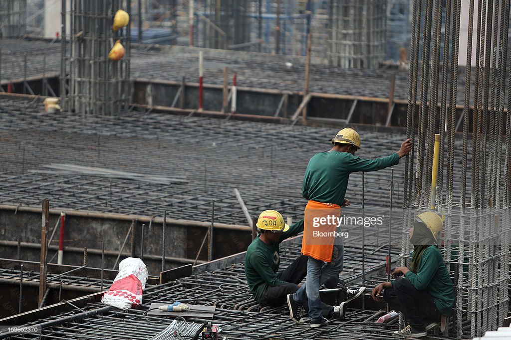 Construction workers chat on a building site at Siam Square in Bangkok, Thailand, on Wednesday, Jan. 23, 2013. Prime Minister Yingluck Shinawatra's government last month approved a new round of increases in the daily minimum wage to 300 baht ($9.8) from the beginning of this year, after a similar raise in April in seven provinces including Bangkok. Photographer: Dario Pignatelli/Bloomberg via Getty Images