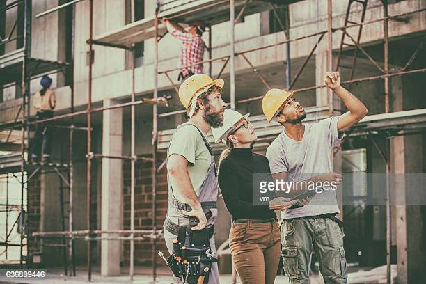Construction workers consulting an architect