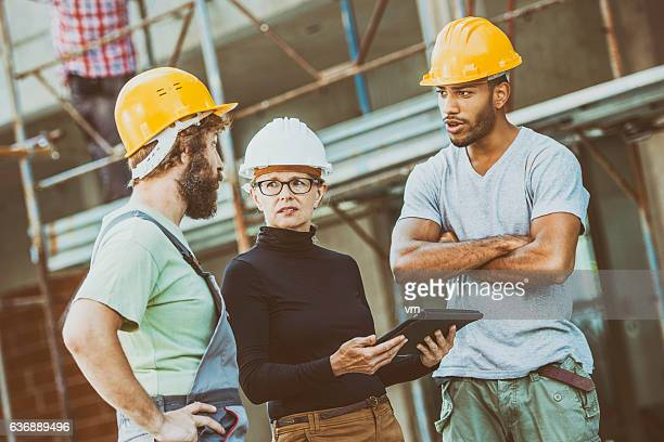 Construction workers consulting female architect