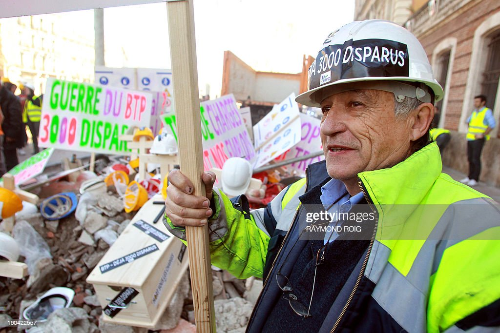 Construction workers demonstrate after emptying rubble in front of the police station in Perpignan as they protest against high employer taxes on January 31, 2013. AFP PHOTO / RAYMOND ROIG