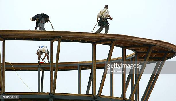 Construction workers do a balance–beam ballet on top of a circular structure that will be a new LA Fitness center at Jamboree at the I–5 Freeway in...