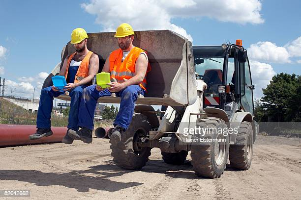 2 construction workers eating lunch on digger