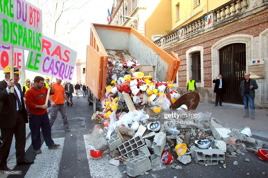 Construction workers empty rubble in front of the police station in Perpignan as they protest against high employer taxes on January 31, 2013. AFP PHOTO / RAYMOND ROIG
