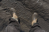 Construction worker's feet in mud of tyre track
