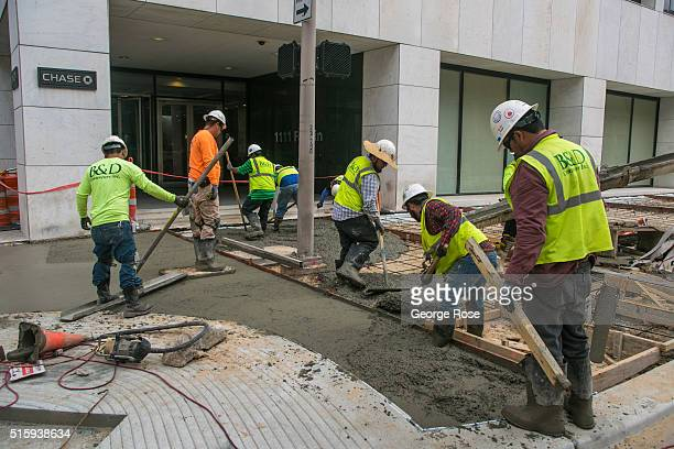 Construction workers finish paving downtown sidewalks on February 29 2016 in Houston TX Despite the plunge in oil prices Houston the corporate energy...