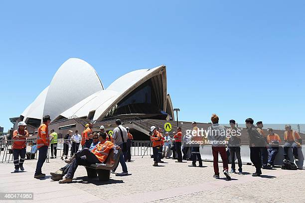 Construction workers gather in front of the Sydney Opera House after being evacuated on December 15 2014 in Sydney Australia Major landmarks in...