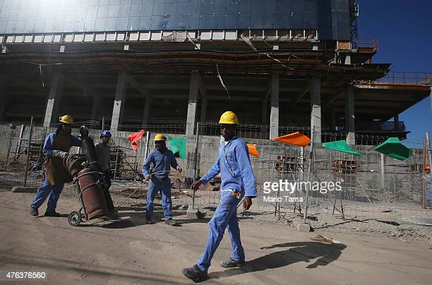 Construction workers gather in the Vila Autodromo 'favela' community with Olympic Park construction ongoing on June 8 2015 in the Barra da Tijuca...
