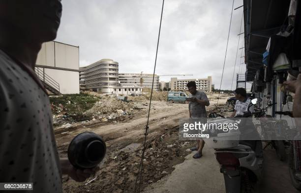 Construction workers gather outside their temporary residence near the construction site of the Evergrande International Hospital inside the Hainan...